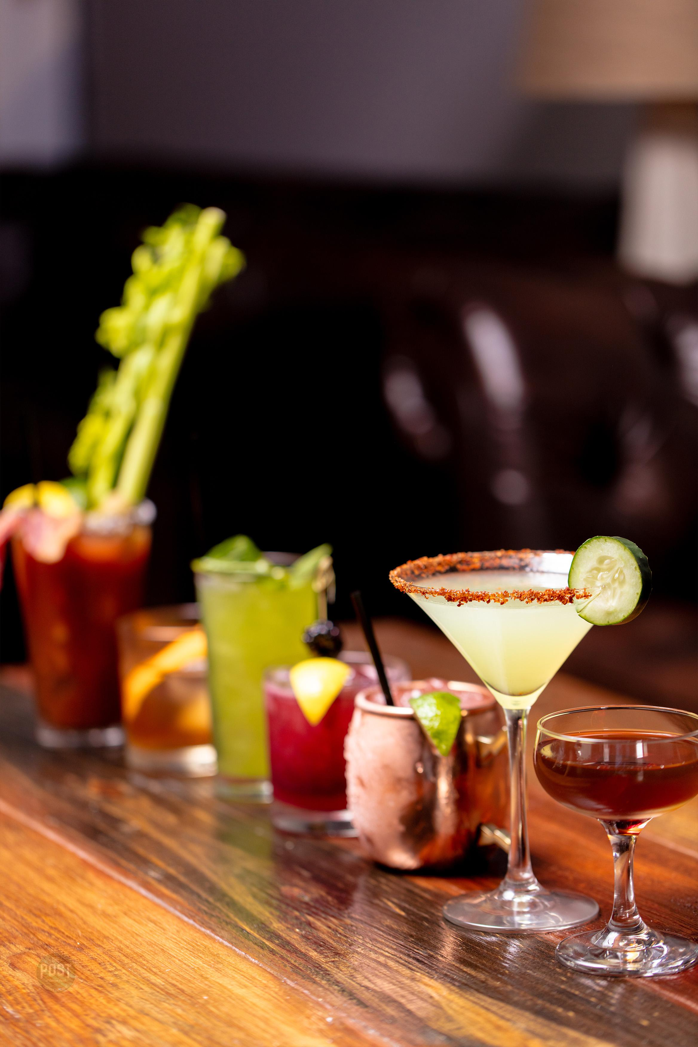 A line of delicious hand-crafted cocktails lined up on wood bar